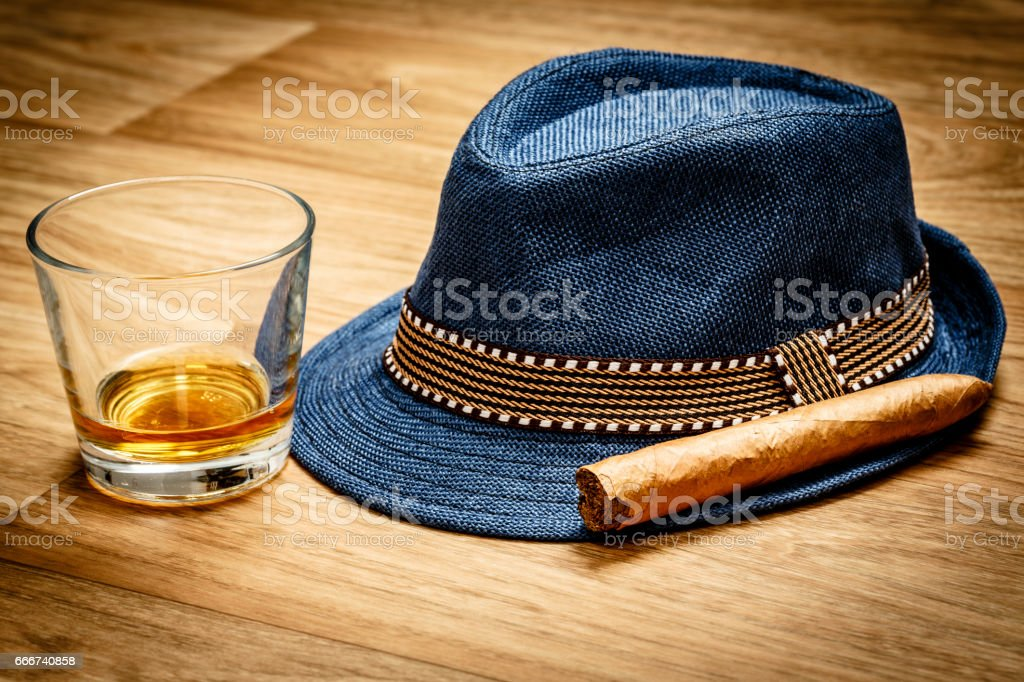 blue hat with cigar and expensive drink of whisky or rum on wooden floor stock photo