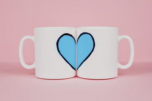 istock Blue heart drawn on two cups on pink background 1093648044