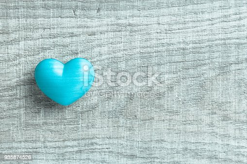 istock Blue heart shape over wooden table. Symbol of valentine day for background use. Concept of love and romance. Color filter. 935874526