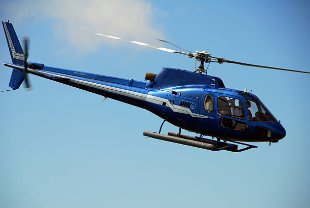 Blue helicopter flying against the blue sky stock photo