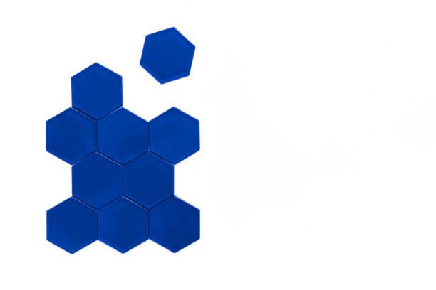 Mavi altıgenler beyaz arka plan üzerinde bir arı kovanı oluştururlar. Bir altıgen figürden ayrılır. Süspansiyon kavramı. Kopyalama alanı stok fotoğrafı