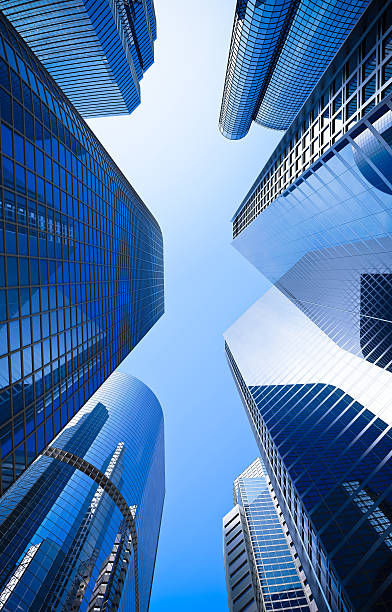 blue highrise glass skyscraper street low angle shot street of highrise glass skyscraper buildings low angle shot in blue dominant against a clear sky skyscraper stock pictures, royalty-free photos & images