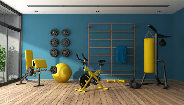 Blue home gym with black and yellow fitness equipment stock photo