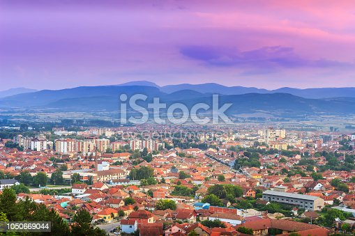 Colorful purple sunset sky over Pirot city in Serbia and golden, sunlit buildings