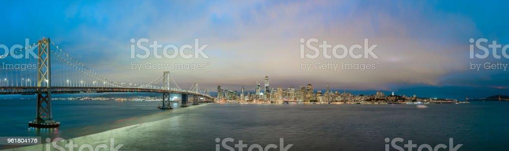 Blue hour panorama of San Francisco skyline with Bay Bridge. stock photo