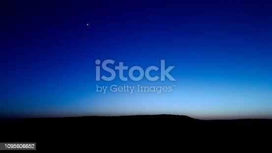 The scene of blue hour which splits night and day times. In the scene there are also the moon and a bright star through a blue sky. I kept the foreground black to assure this amazing sky scene.