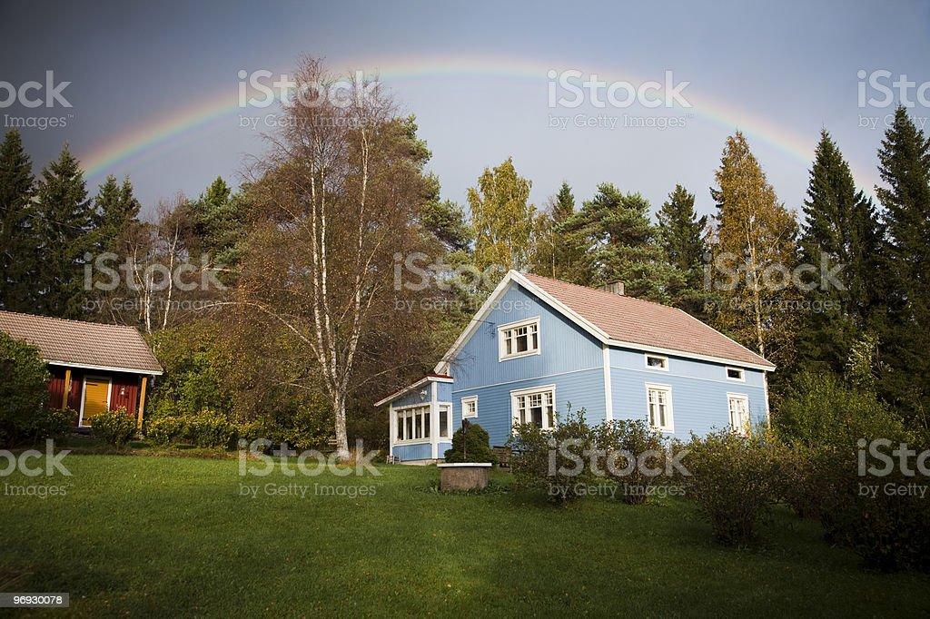 Blue house under rainbow royalty-free stock photo