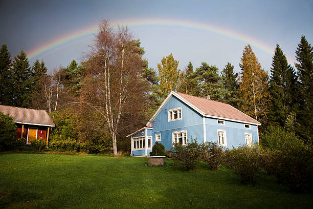 Blue house under rainbow stock photo