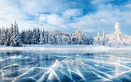 istock Blue ice and cracks on the surface of the ice. Frozen lake under a blue sky in the winter. The hills of pines. Winter. Carpathian, Ukraine, Europe. 853844276
