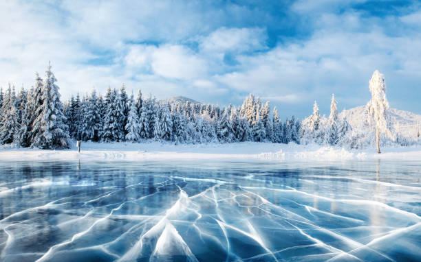 아이스 블루 고 얼음의 표면에 균열. 겨울에 푸른 하늘 아래 얼어붙은 호수. 소나무 언덕입니다. 겨울입니다. 카 르 파티 아, 우크라이나, 유럽입니다. - 눈 냉동상태의 물 뉴스 사진 이미지