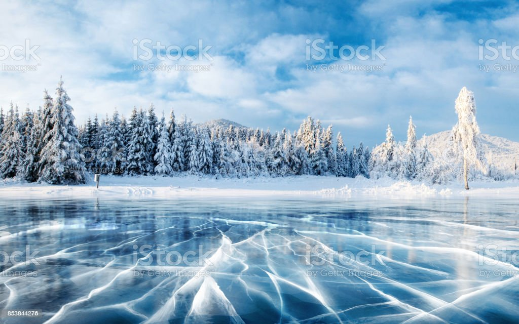 Blue ice and cracks on the surface of the ice. Frozen lake under a blue sky in the winter. The hills of pines. Winter. Carpathian, Ukraine, Europe. stock photo