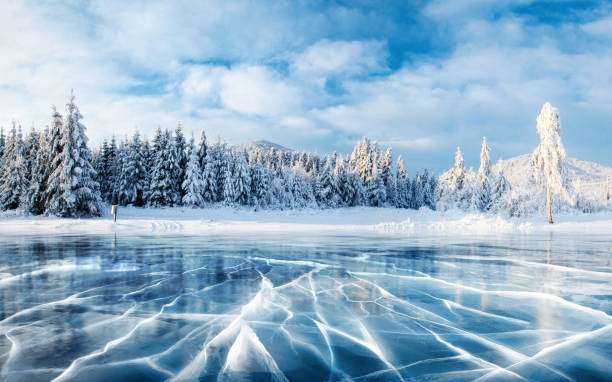 blue ice and cracks on the surface of the ice. frozen lake under a blue sky in the winter. the hills of pines. winter. carpathian, ukraine, europe. - non urban scene stock pictures, royalty-free photos & images