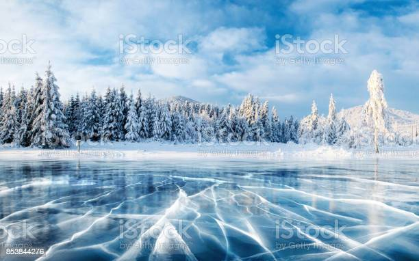 Photo of Blue ice and cracks on the surface of the ice. Frozen lake under a blue sky in the winter. The hills of pines. Winter. Carpathian, Ukraine, Europe.