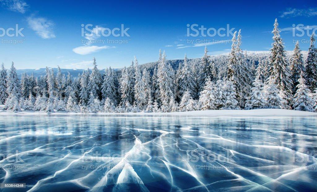 Blaues Eis und Risse auf der Oberfläche des Eises. Zugefrorenen See unter blauem Himmel im Winter. Die Hügel von Kiefern. Winter. Karpaten, Ukraine, Europa. – Foto