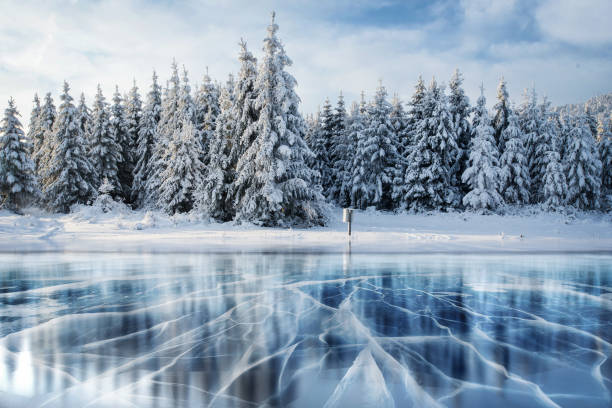 blue ice and cracks on the surface of the . - frozen stock photos and pictures