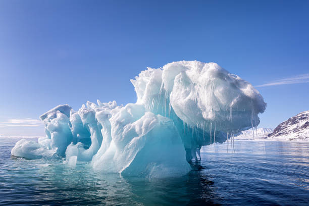 Blue ice iceberg floating in the arctic waters of Svalbard Blue ice iceberg, formed when a glacier calves, floating in the arctic waters of Svalbard, a Norwegian archipelago between mainland Norway and the North Pole glacier stock pictures, royalty-free photos & images