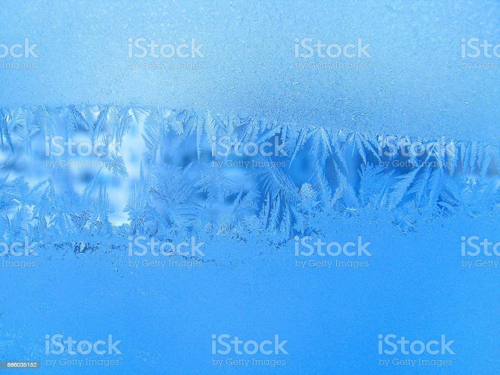 Blue ice natural pattern on winter window glass stock photo