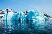 'Blue iceberg floating in the Hornsund Spitzbergen. Blue ice is very old ice, which was under pressure by the glacier. The cloudy, fogy weather is typical for the north and the light show the wide spectrum of the blue colors.'
