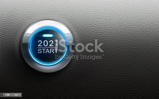 Blue illuminated start 2021 metal button on black leather backgound