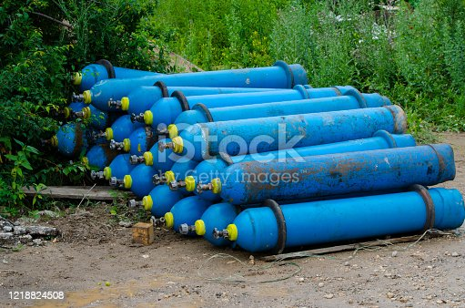 Blue industrial oxygen cylinders on the ground in the mud Unsafe storage of industrial waste Selective focus