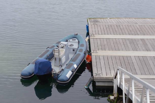 blauen schlauchboot an der pier festgemacht - rudermaschine stock-fotos und bilder