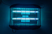 Blue insect zapper that is switched on and working away in Africa