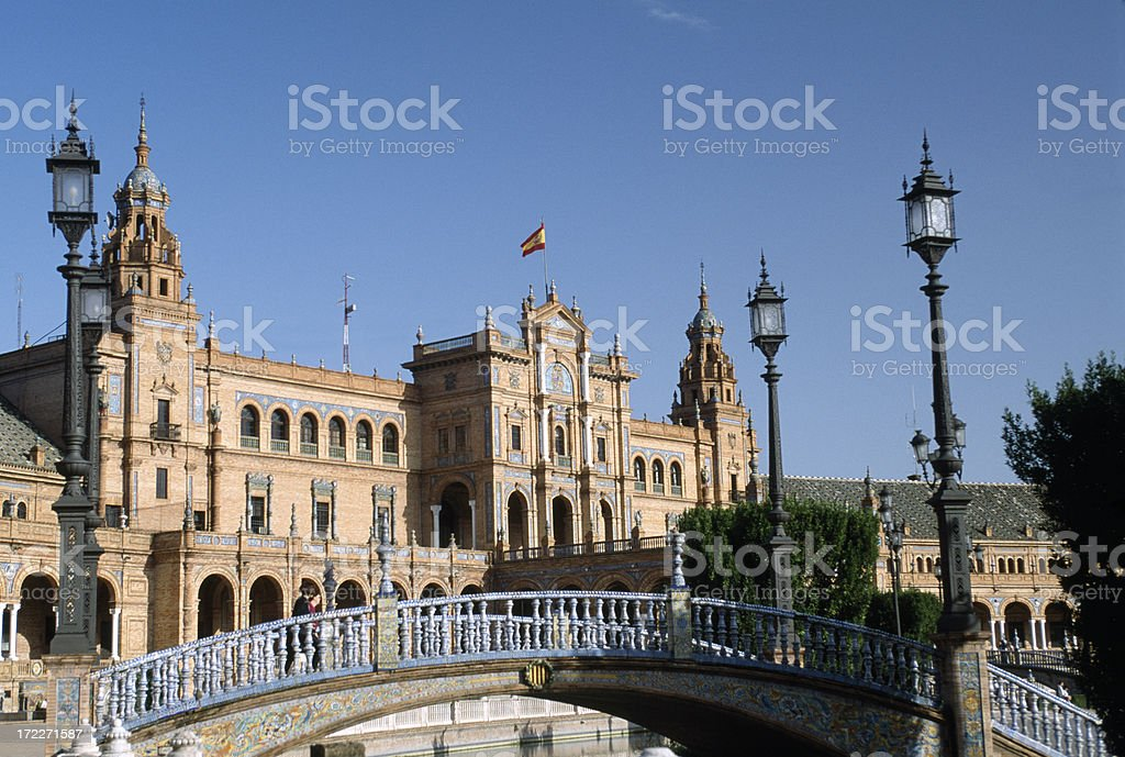 A blue iron bridge in front of the ornate Plaza de Espana. royalty-free stock photo