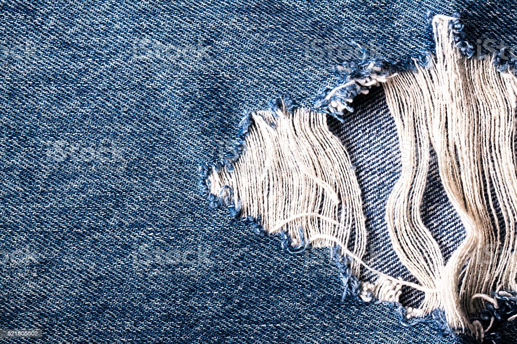 blue jean texture with hole and threads showing stock photo