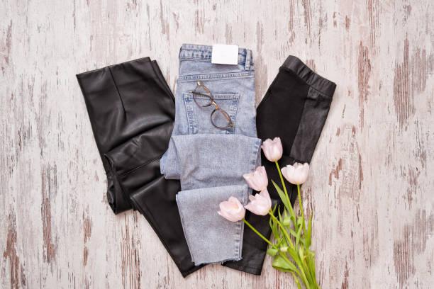 blaue jeans und schwarze leder-leggins, brille, rosa tulpen. mode-konzept. ansicht von oben - leder leggings stock-fotos und bilder