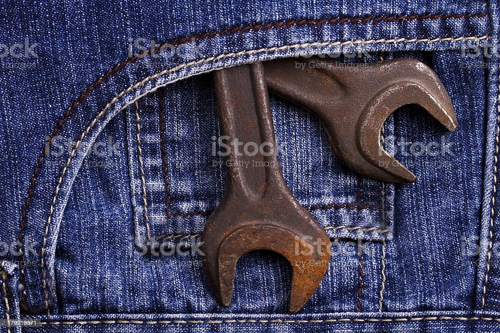 Blue jeans pocket with lug wrench royalty-free stock photo