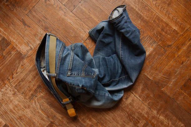 blaue jeans geworfen auf holzboden - anti unordnung stock-fotos und bilder
