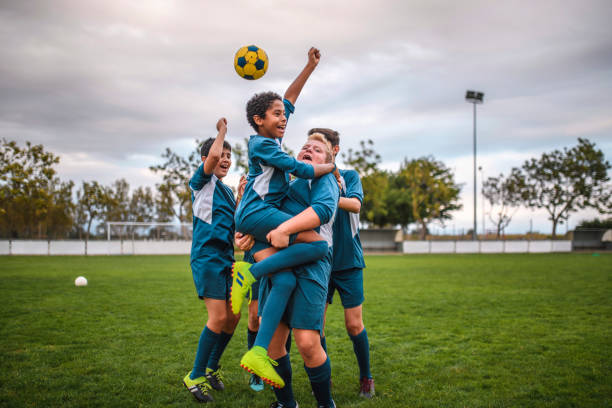 Blue Jersey Boy Footballers Cheering and Celebrating stock photo