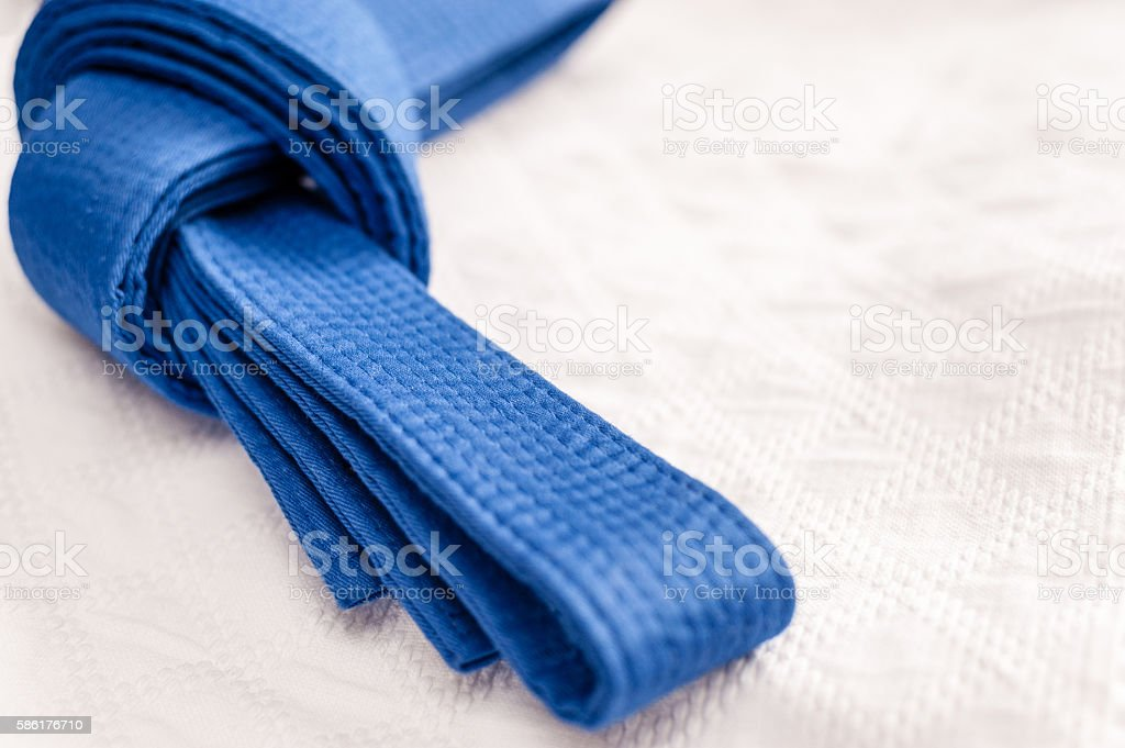 Blue judo belt on white kimono stock photo