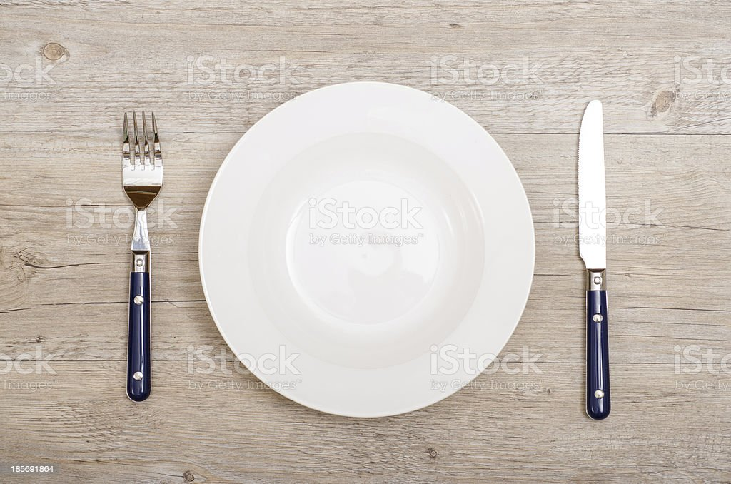 Blue knife and fork with white plate royalty-free stock photo