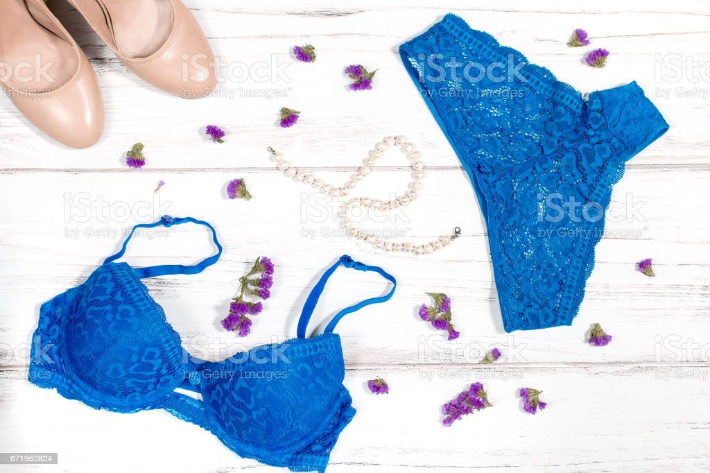 Blue lacy lingerie set with pearl necklace and nude shoes stock photo