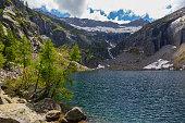 blue lago di Tomeo lake in Swiss alpine mountains in Ticino, clouds