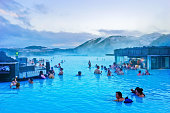Blue Lagoon, Iceland - January 27, 2017: View of the Blue Lagoon pool at dusk with lots of tourists bathing in Blue Lagoon, Iceland on January 27, 2017.