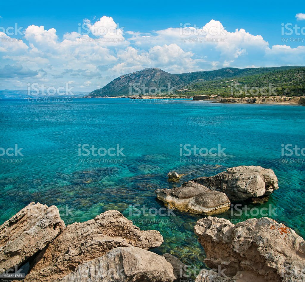 blue lagoon with rocks at foreground and mountains at background stock photo