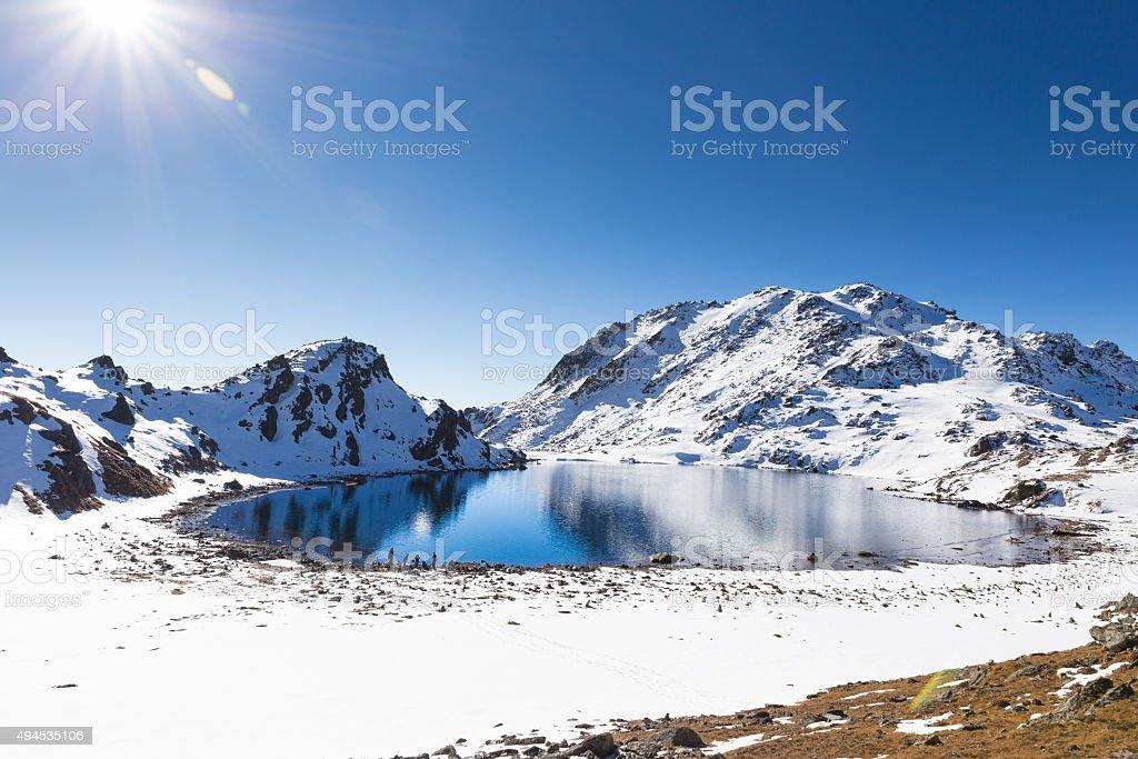 Blue lake mountains covered snow, Gosaikunda Nepal. stock photo