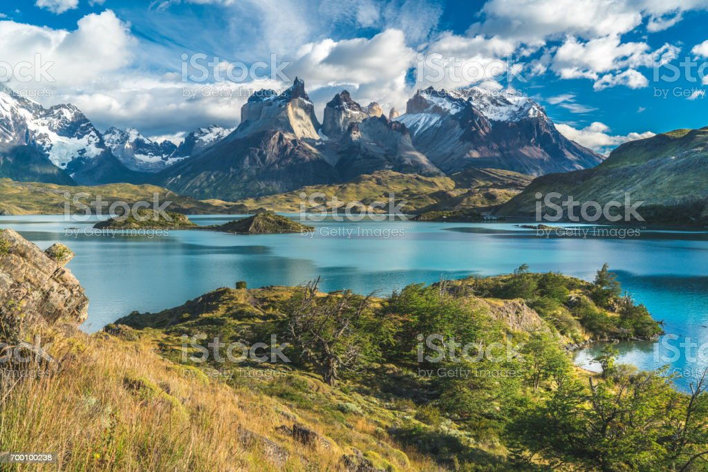 Blue lake on a snowy mountains background and cloudy sky Torres del paine stock photo