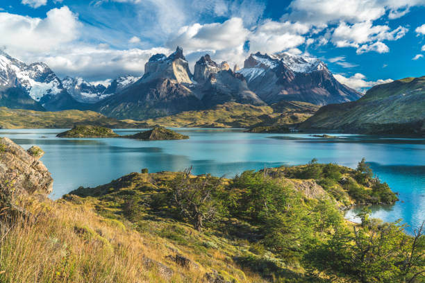 blue lake on a snowy mountains background and cloudy sky torres del paine - mountain range stock photos and pictures