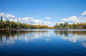 istock Blue lake with treeline in autumn color on a sunny afternoon in northern Minnesota 1280015859