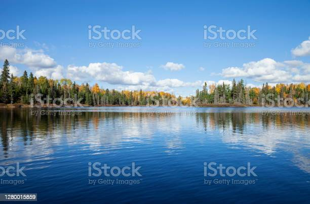 Photo of Blue lake with treeline in autumn color on a sunny afternoon in northern Minnesota