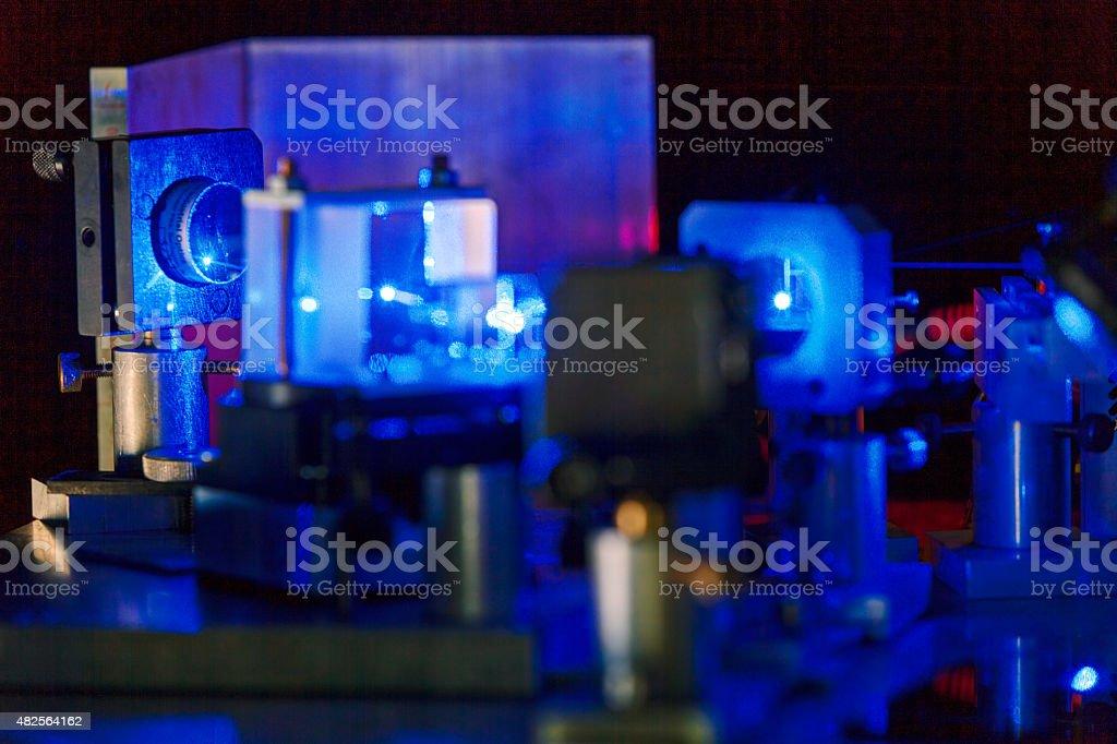 Blue laser in a quantum optics lab. stock photo