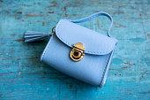 Blue leather Women's handbag on wood background