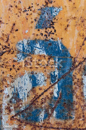 184953872istockphoto blue letter with tilde scratched rusty metal background 1084642262