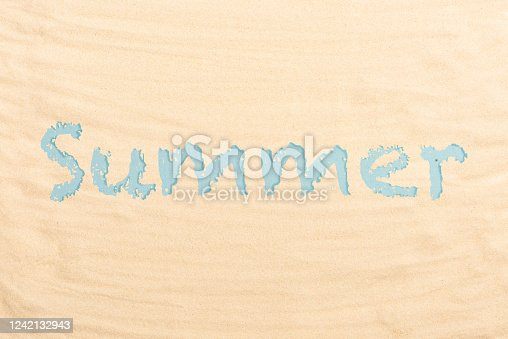 Blue letters summer on a beach sand. Flat lay, top view