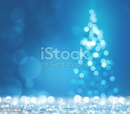 872229066 istock photo Blue light and christmas tree on white defocused sparkles 1076220646