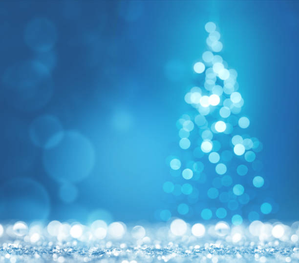Blue light and christmas tree on white defocused sparkles stock photo