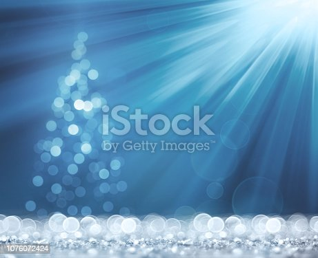 872229066 istock photo Blue light beam and christmas tree on white defocused sparkles 1076072424